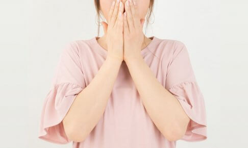 びっくりして両手で口を抑える女性